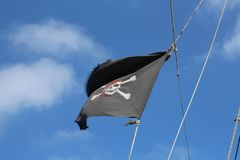 A pirate flag is developing in the sky. The flag is black with a skull royalty free stock photo