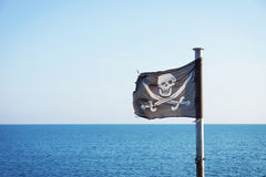 Pirate flag fluttering in the breeze Royalty Free Stock Image