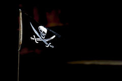 Pirate flag  flying on a black background Royalty Free Stock Image