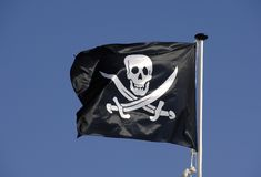 Pirate flag flying in blue sky royalty free stock photos