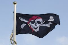 A pirate flag flying on a sunny day. Skull and cross bones, jolly rodger flag flying in Glasgow on a sunny winter day stock image