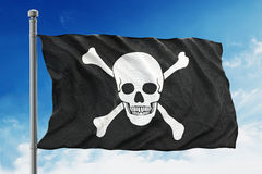 Pirate flag waving on blue background Stock Photo
