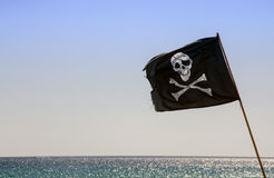 Pirate flag waving with blue sea background. At the sea in sunny day Stock Photo