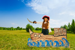 Pirate girl with black hat, sword stands on ship Stock Photography