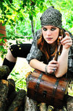 Pirate girl with knife. Beautiful redheaded pirate girl is touching knife royalty free stock image