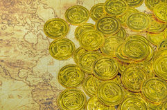 Pirate golden coin on a old world map Royalty Free Stock Photography
