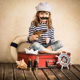 Pirate. Happy kid pirate playing with toy sailing boat indoors. Travel and adventure concept stock photos