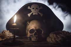 Pirate hat above a human skull. Human skull with pirate captain hat above, burning candle, seashell and mooring rope on the wooden table in the mystic smoke stock photography