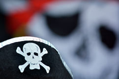 Pirate hat with skull and bones sign and Jolly Roger flag Stock Photo