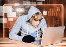 Pirate informatique à l'aide d'un ordinateur portable et tenant une carte de crédit devant le fond orange numérique photo stock