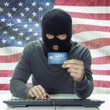 Pirate informatique à la peau foncée avec le drapeau sur le fond jugeant la carte de crédit disponible - les Etats-Unis Photos libres de droits