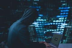 Pirate informatique anonyme avec l'ordinateur portable devant la sécurité de cyber de code binaire Photographie stock libre de droits
