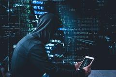 Pirate informatique anonyme avec le comprimé devant la sécurité de cyber de code binaire Image stock