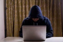 Pirate informatique asiatique entaillant le réseau informatique avec l'ordinateur portable Photos libres de droits