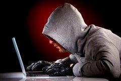 Pirate informatique avec l'ordinateur portable photos stock