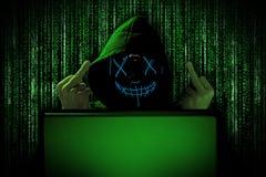 Pirate informatique avec le masque rougeoyant bleu derrière l'ordinateur portable de carnet devant l'attaque verte d'entaille de photographie stock