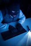 Pirate informatique dactylographiant sur le clavier Images libres de droits