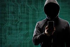 Pirate informatique dangereux avec un instrument de smartphone au-dessus de fond num?rique avec le code binaire Visage fonc? obsc image libre de droits