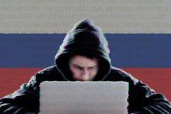 Pirate informatique dans une obscurité hoody avec le drapeau russe utilisant l'ordinateur portable photographie stock libre de droits