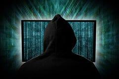 Pirate informatique derrière l'affichage rougeoyant de moniteur d'ordinateur devant l'ordinateur vert d'entaille de cyber d'Inte photo stock