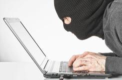 Pirate informatique en code de virus d'écriture de passe-montagne sur le clavier d'ordinateur portable Photo stock