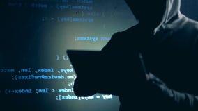 Pirate informatique masculin déguisé dans un hoodie et une projection des données d'ordinateur clips vidéos