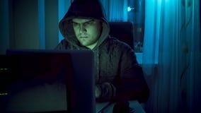 Pirate informatique masculin dans le hoodie travaillant sur l'ordinateur portable la nuit Images stock