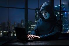 Pirate informatique masqué avec un ordinateur portable images libres de droits