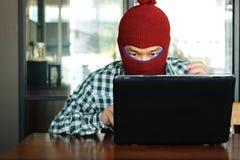 Pirate informatique masqué utilisant un passe-montagne volant des données d'ordinateur portable Concept de garantie d'Internet Photos stock