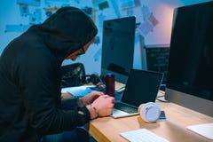 pirate informatique menotté dans le hoodie devant l'ordinateur portable image stock