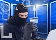 Pirate informatique observant une carte de crédit à un centre de traitement des données Photos libres de droits