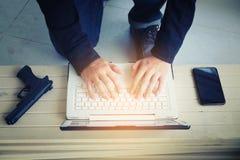 Pirate informatique tenant l'arme à feu travaillant sur son ordinateur, guerre, terrorisme, ter photo libre de droits