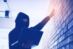 Pirate informatique tenant l'arme à feu travaillant sur son ordinateur, guerre, terrorisme, ter photographie stock