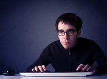 Pirate informatique travaillant avec le clavier sur le fond bleu Images stock