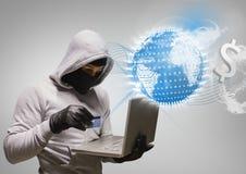 Pirate informatique travaillant sur l'ordinateur portable devant la terre numérique sur le fond gris Photos stock