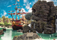 Pirate island. Pirate ship in the backwater of tropical pirate island, with big rock in form of skull near it Stock Photos