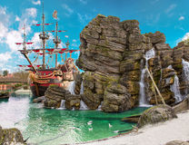 Pirate island. Pirate ship in the backwater of tropical pirate island, with big rock in form of skull near it Stock Photography