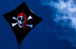 Pirate kite. Closeup of black kite decorated with skull and crossbones as seen on pirate flags, dark brooding sky background  with hazy clouds Royalty Free Stock Photography