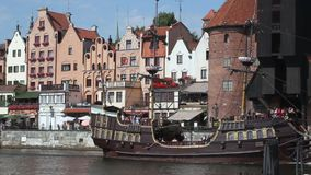 Pirate-like tourist sailing ship moving along waterfront of old medieval city. Stock footage stock video footage