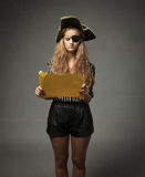 Pirate looking for treasure with yellow map. Dark background stock images