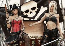 Pirate plunder. Two pirate females showing off there looted treasure of gold coins. Stock Image