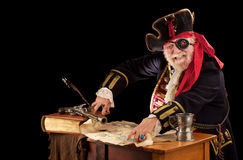 Pirate pointing at his treasure map. Gleeful old pirate captain sits at his table with still life of log book, quill pen, musket, pewter mug, and tattered royalty free stock photos
