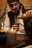 Pirate pour out white rum, concept medieval and themeparty Stock Image