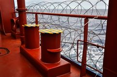 Pirate protection measures onboard of a merchant ship passing pirate high risk area, Babed wire on a ship railing stock photography