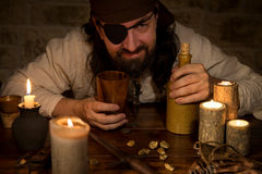 Pirate with rum and a lots of candles and goldnuggets, concept m. A pirate with rum and a lots of candles and goldnuggets, concept medieval and Themeparty royalty free stock photography
