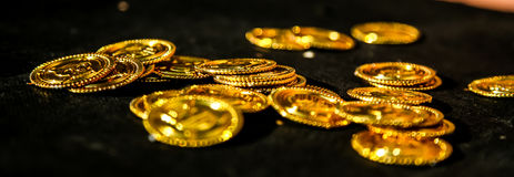 Pirate`s Booty. Golden coins on a black cloth Royalty Free Stock Photography