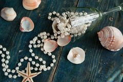 The pirate`s treasure - white pearls and shells on blue wooden background, vintage fashion Royalty Free Stock Photo