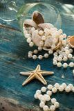 The pirate`s treasure - white pearls and shells on blue wooden background, vintage fashion Stock Image