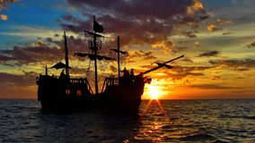 Pirate ship in the caribbean sea. A pirate ship sails at sunset in the caribbean sea with beautiful blue clouds Stock Photography