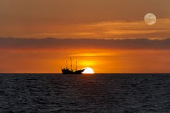 Pirate Ship Fantasy. Pirate ship sunset  is sailing at sea silhouetted against a setting sun and a colorful cloudy filled sky Royalty Free Stock Photography